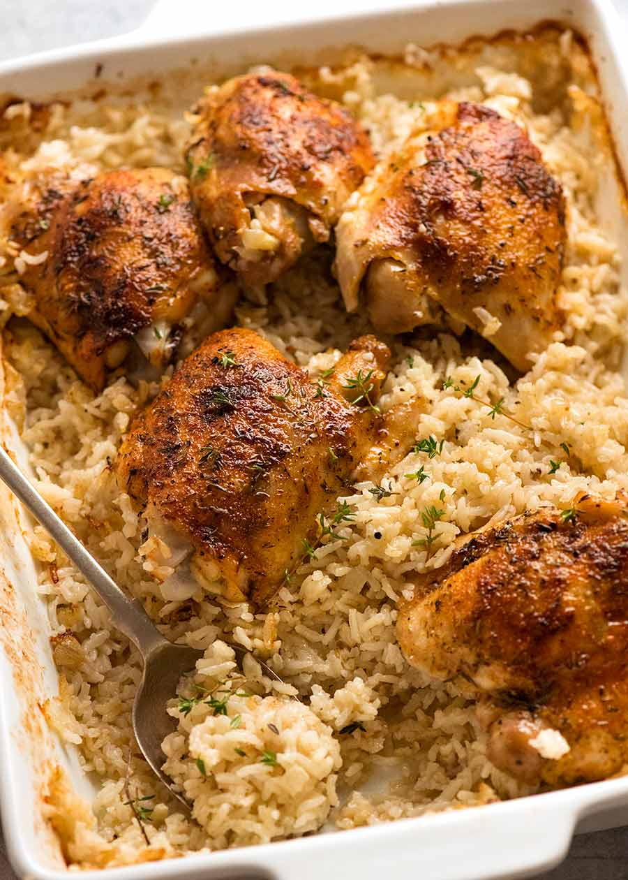 White baking dish with Oven Baked Chicken and Rice, ready to be served